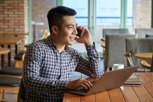 vue-cote-homme-asiatique-ayant-appel-telephonique-tout-travaillant-ordinateur-portable_1098-18467.jpg