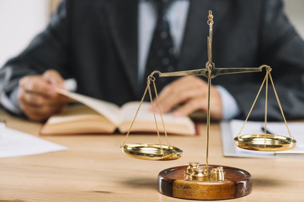 echelle-justice-or-devant-avocat-lisant-livre-table_23-2147898544.jpg